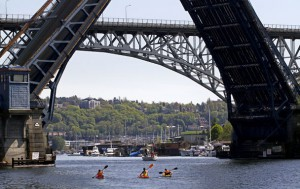 Ellen M. Banner / The Seattle Times  Kayakers head toward the Fremont Bridge, while the Aurora Bridge looms above it.
