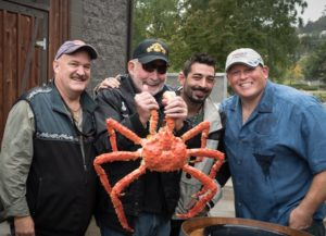 Photo by Jeff Pond  Industry legend Captain Chuck Bundrant, founder of Trident Seafoods, hoists an Alaskan crab. He's joined by Captain Keith Colburn of the F/V Wizard and Captain Josh Harris and Captain Casey McManus of the F/V Cornelia Marie.