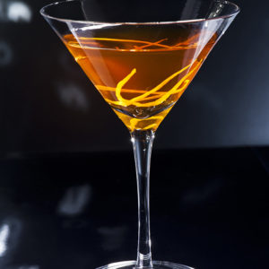Manhattan cocktail over black and bright sparkles